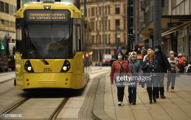 Pedestrians wearing a face mask or covering due to the COVID19 pandemic walks past a tram in Manchester northwest England on August 3 following a...