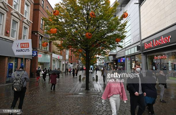 Pedestrians wearing a face mask or covering due to the COVID-19 pandemic, walks past a tree decorated in pumpkins ahead of Halloween, in Manchester,...