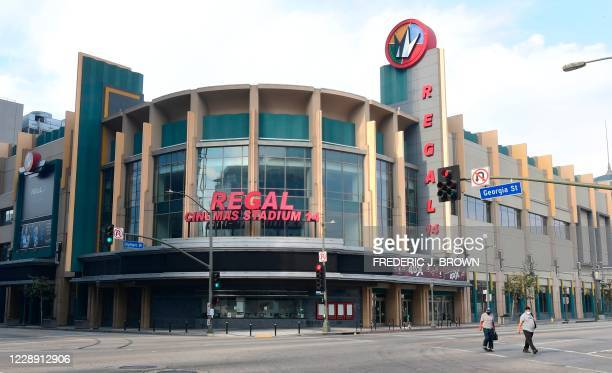 Pedestrians wearing a facemasks due to the coronavirus pandemic cross the street in front of Regal Cinemas L.A. Live on October 5, 2020 in Los...