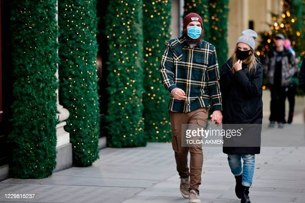 Pedestrians wearing a masks because of the novel coronavirus pandemic walk past a store front covered in Christmas decorations in central London on...