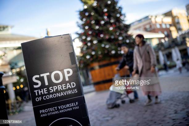 """Pedestrians wearing a protective face covering to combat the spread of the coronavirus, pass COVID-19 information sign reading """"STOP the spread"""" as..."""