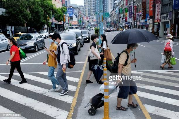 Pedestrians, wearing face masks after Taiwan bumped up its alert level in some locations in the wake of a new wave of Covid-19 coronavirus...