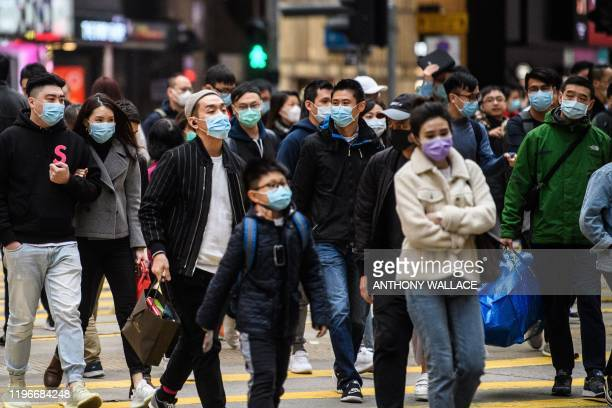 TOPSHOT Pedestrians wearing face masks cross a road during a Lunar New Year of the Rat public holiday in Hong Kong on January 27 as a preventative...
