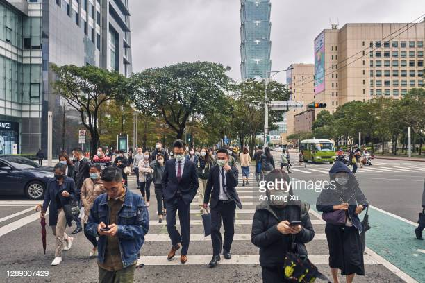 Pedestrians wearing face masks cross a street on December 02, 2020 in Taipei, Taiwan. Taiwan imposed mandatory mask-wearing regulations in some...