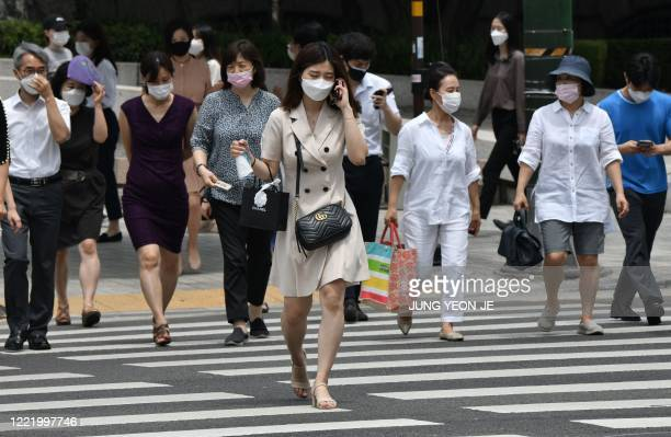Pedestrians wearing face masks cross the road in central Seoul on June 23, 2020. - South Korea reported 46 new coronavirus cases on June 23 after...