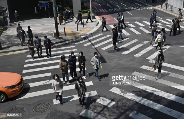 TOPSHOT Pedestrians wearing face masks cross the road in Seoul on April 23 2020 South Korea's economy saw its worst performance in more than a decade...