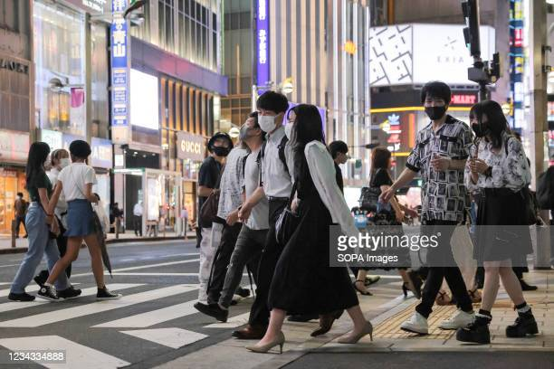 Pedestrians wearing face masks cross the road in Shinjuku. 3300 people have tested positive for the Novel Coronavirus on day eight of the Tokyo 2020...