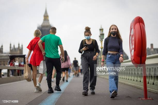 Pedestrians wearing face masks cross Westminster Bridge with Elizabeth Tower, better known by the nickname for the Great Bell in the clock Big Ben in...