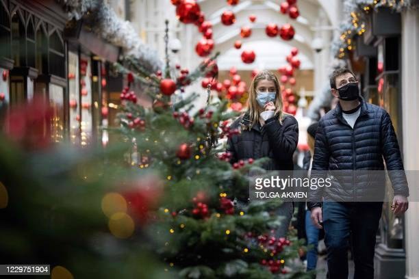 Pedestrians wearing face masks due to the COVID-19 pandemic, walk past Christmas-themed window displays inside Burlington Arcade in central London,...