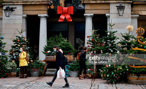 Pedestrians wearing face masks or coverings due to the COVID-19 pandemic, walk past Christmas trees in Covent Garden in central London on November...