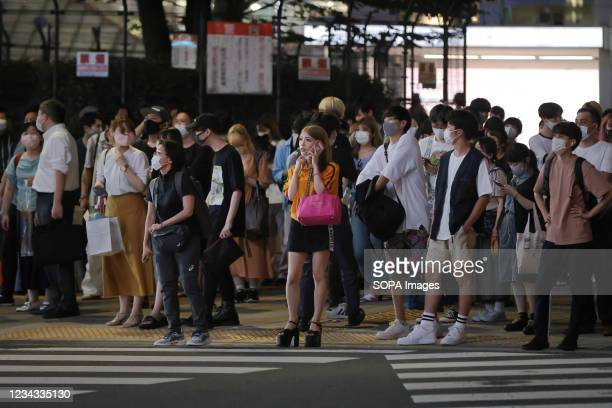 Pedestrians wearing face masks wait for a green light at a cross road in Shinjuku. 3300 people have tested positive for the Novel Coronavirus on day...