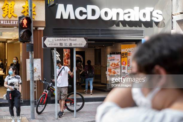 Pedestrians wearing face masks wait to cross the street in front of the American multinational fastfood hamburger restaurant chain McDonald's in Hong...