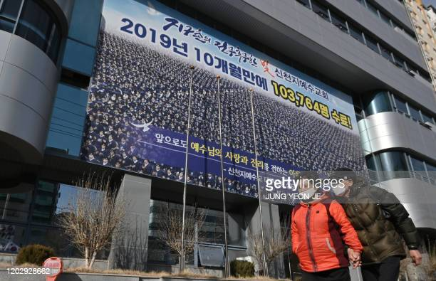 Pedestrians wearing face masks walk in front of the Daegu branch of the Shincheonji Church of Jesus in the southeastern city of Daegu on February 24,...