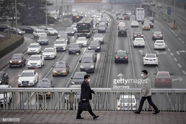 Pedestrians wearing face masks walk on a footbridge as vehicles move through a highway in Beijing, China, on Friday, Jan. 6, 2017. Toxic haze that...