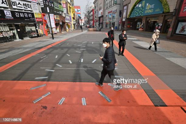 Pedestrians wearing face masks walk on the street at Dongseongro shopping district in the southeastern city of Daegu on February 21, 2020. - South...