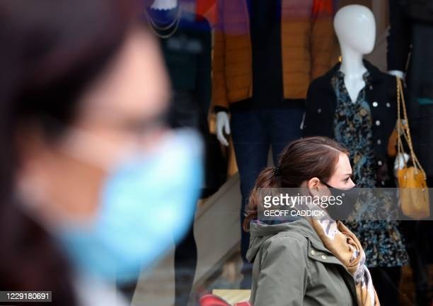 Pedestrians wearing face masks walk past a clothes shop in Cardiff, south Wales on October 20 ahead of a short, two-week lockdown due to begin on...