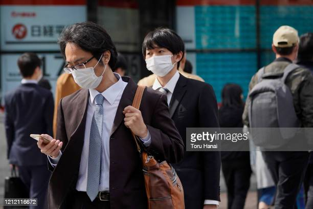 Pedestrians wearing face masks walk past a monitor displaying the Nikkei 225 index outside a securities firm on March 13 2020 in Tokyo Japan Prime...