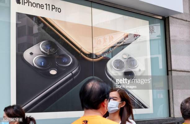 Pedestrians wearing face masks walk past American multinational technology company Apple Iphone 11 Pro advertisement in Hong Kong