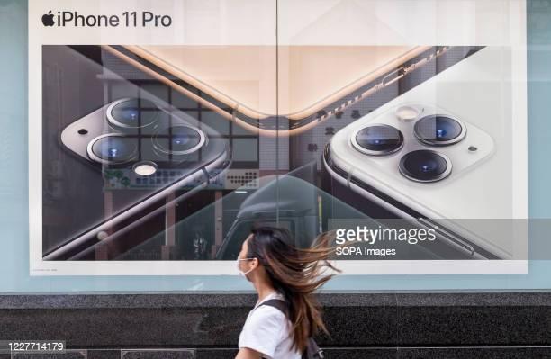 Pedestrians wearing face masks walk past American multinational technology company Apple Iphone advertisement in Hong Kong