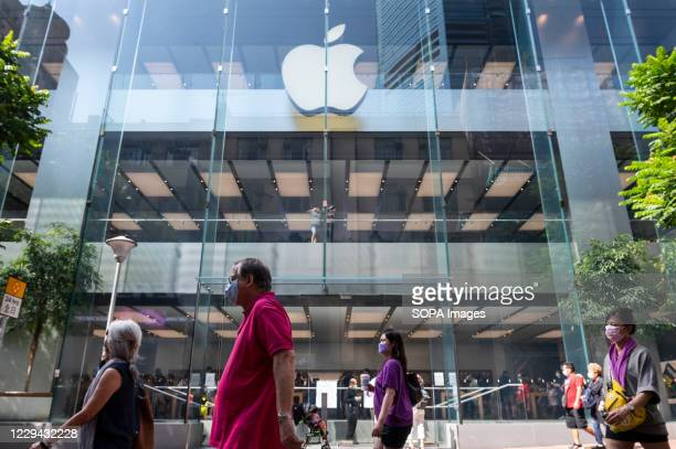 Pedestrians wearing face masks walk past an American multinational technology company Apple store in Hong Kong