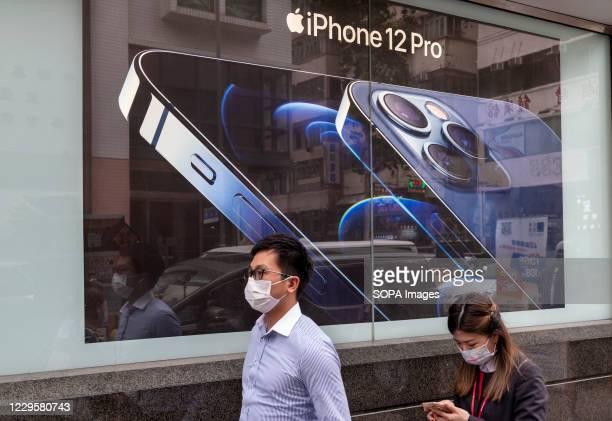 Pedestrians wearing face masks walk past an American multinational technology company Apple Iphone 12 Pro advertisement in Hong Kong.