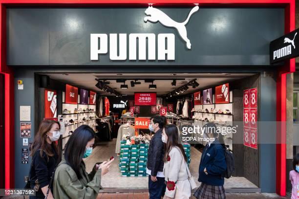 Pedestrians wearing face masks walk past German multinational sportswear brand, Puma store in Hong Kong.