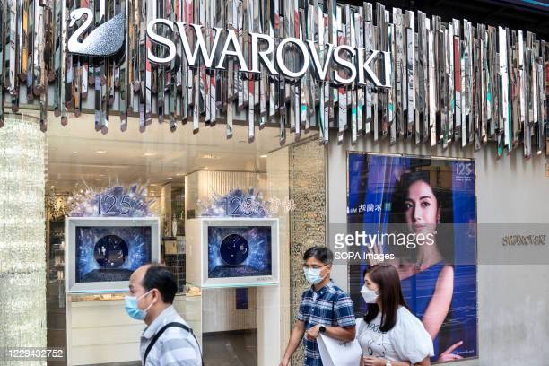 Pedestrians wearing face masks walk past the Austrian jewelry producer and luxury brand Swarovski store in Hong Kong