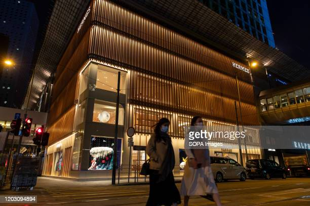 Pedestrians wearing face masks walk past the Hermès brand store and logo in Hong Kong The deadly coronavirus has caused the Chinese economy to slow...