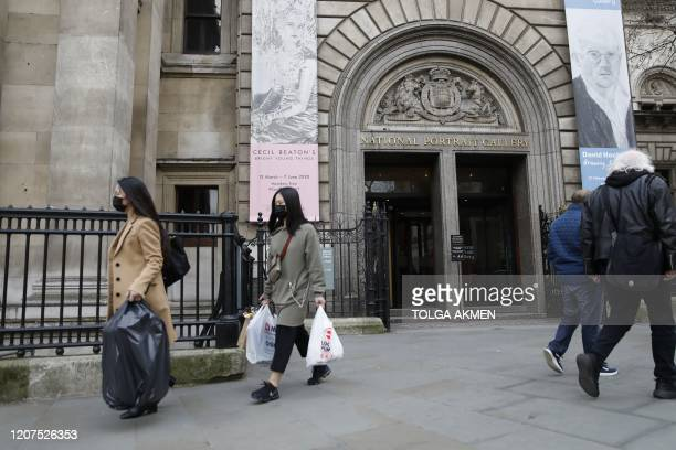 Pedestrians wearing face masks walk past the National Portrait Gallery in central London on March 17, 2020 after it was announced that the gallery...