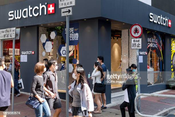 Pedestrians wearing face masks walk past the Swiss multinational watchmaker Swatch brand store in Hong Kong