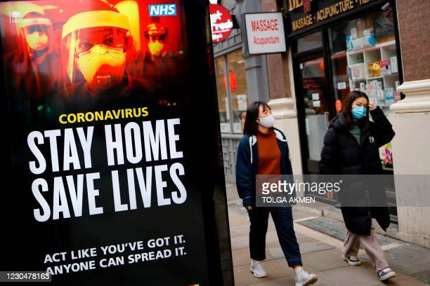 """Pedestrians wearing facemasks walk past NHS signage promoting """"Stay Home, Save Lives"""" on a bus shelter in Chinatown, central London on January 8 as..."""