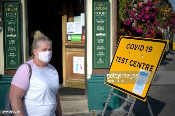 Pedestrians wearing facemasks walks past a sign for a Covid19 test centre in Leyton east London on September 19 2020
