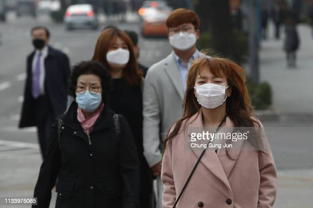 Pedestrians wearing mask walk during a polluted day on March 06 2019 in Seoul South Korea Most of South Korea was blanketed by extraordinarily heavy...