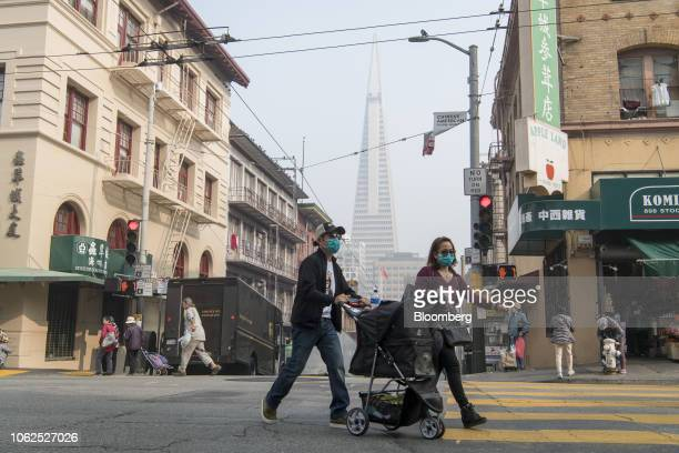 Pedestrians wearing masks cross the street as smoke from the Camp Fire fills the air in San Francisco California US on Friday Nov 16 2018 The Camp...