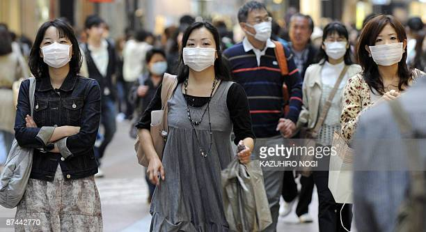 Pedestrians wearing masks walk along a street in downtown Kobe, Hyogo prefecture, in western Japan on May 17, 2009. Japan said on May 17 that nine...