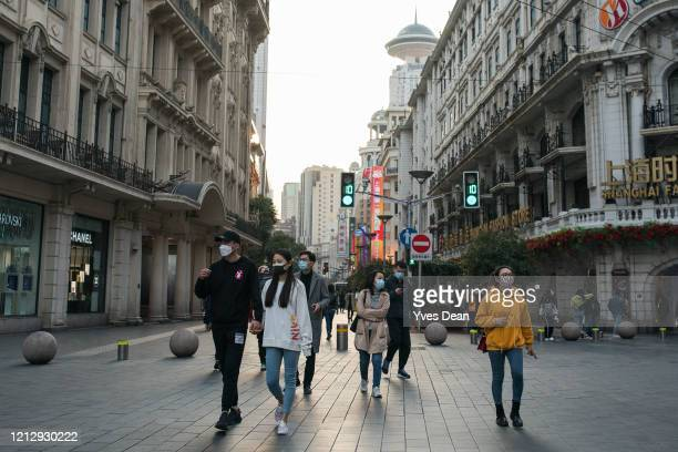 Pedestrians wearing masks walk at Nanjing road commercial area on March 17, 2020 in Shanghai, China. Health authorities of China said the country has...