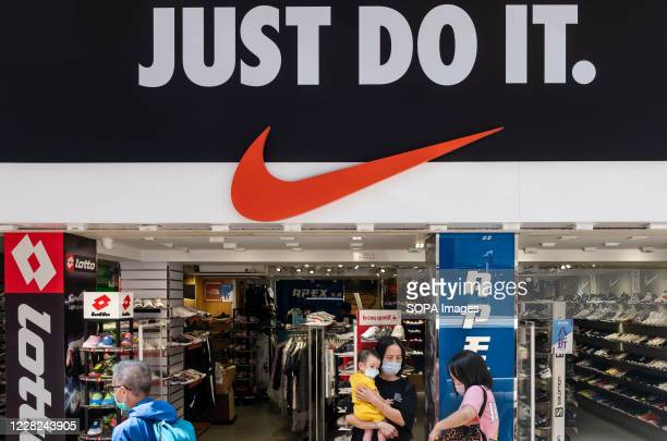 """Pedestrians wearing masks walk past American multinational sport clothing brand Nike store, logo, with a slogan """"Just Do It"""" in Hong Kong."""