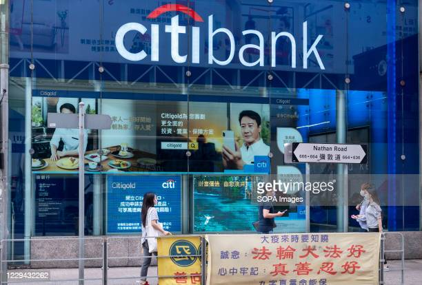 Pedestrians wearing masks walk past the American multinational investment bank and financial services corporation Citibank or Citi branch in Hong Kong