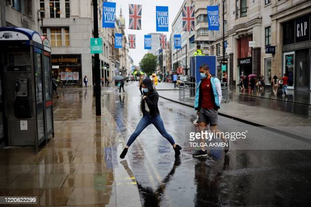 Pedestrians wearing PPE , of a face mask or covering as a precautionary measure against COVID-19, jump over a puddle as they are caught in a downpour...