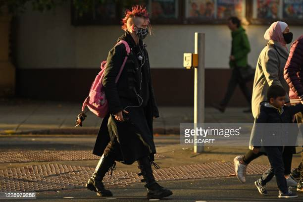 Pedestrians wearing protective face coverings walk through central Nottingham in central England on October 9, 2020. - Pubs and restaurants in...