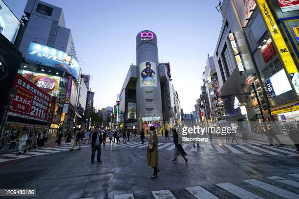 Pedestrians wearing protective face masks cross a road intersection at dusk in the Shibuya district in Tokyo, Japan, on April 8, 2020. Prime...