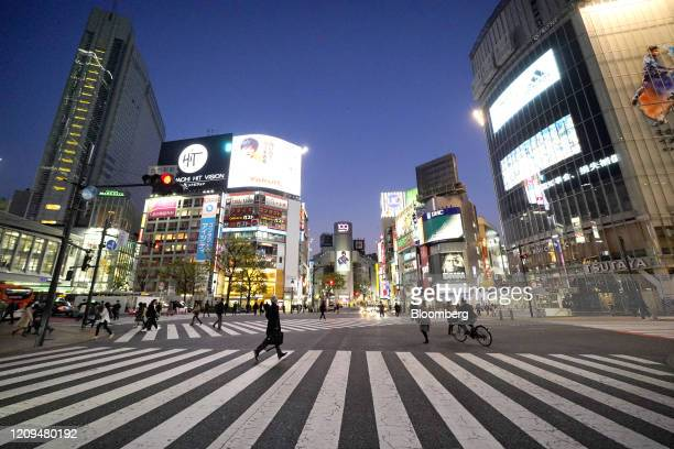 Pedestrians wearing protective face masks cross a road intersection in the Shibuya district in Tokyo Japan on April 8 2020 Prime MinisterShinzo...