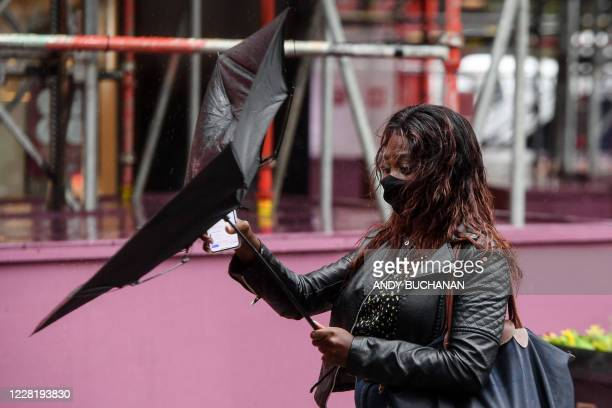 Pedestrians wearing protective face masks struggle against the wind in Glasgow city centre on August 25 as Storm Francis brings rain and high winds...