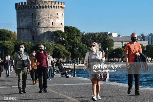 Pedestrians, wearing protective face masks, walk on the waterfront next to the White Tower in Thessaloniki on October 31 as Greek Prime Minister...