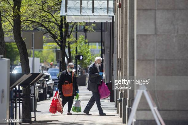 Pedestrians wearing protective masks carry shopping bags in downtown Des Moines, Iowa, U.S., on Friday, May 8, 2020. Governor Kim Reynolds announced...