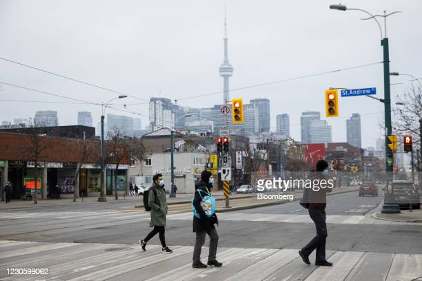 Pedestrians wearing protective masks cross a street in Toronto, Ontario, Canada, on Thursday, Jan. 14, 2021. Ontario's government declared a second...