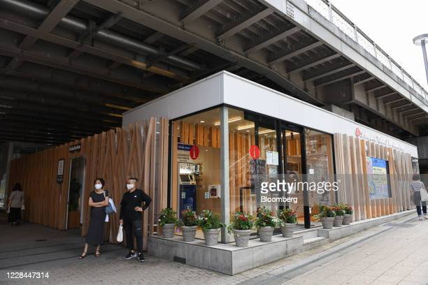 Pedestrians wearing protective masks stand in front of a tourist information office built under railway tracks in the Shinjuku district of Tokyo,...