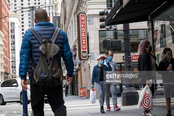 Pedestrians wearing protective masks walk near a Chipotle Mexican Grill Inc restaurant in San Francisco California US on Monday July 20 2020 Chipotle...