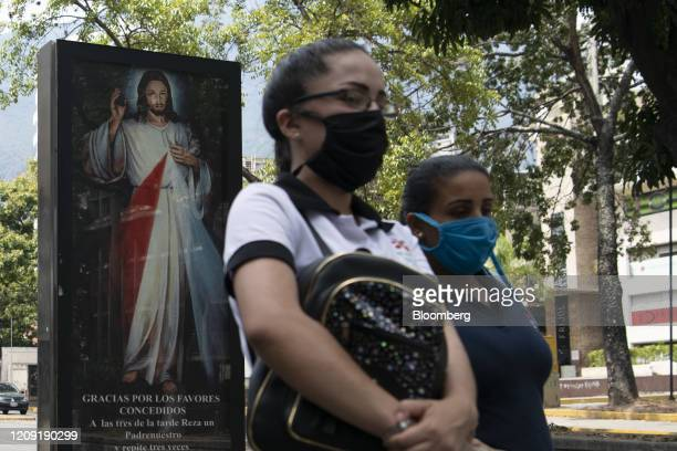 Pedestrians wearing protective masks walk past a billboard with the image of Jesus Christ during Palm Sunday in Caracas Venezuela on Sunday April 5...