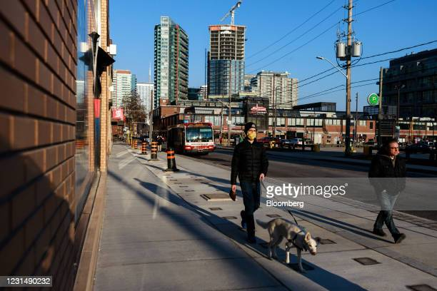 Pedestrians wearing protective masks walk past the Liberty Market Building in the Liberty Village neighborhood of Toronto, Ontario, Canada, on...